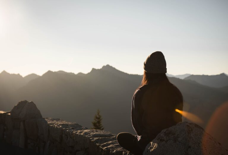 Girl sitting down meditating looking at the sunrise